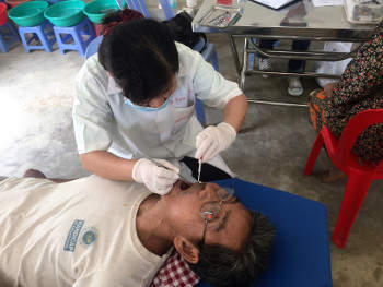 man in dentist chair in rural Cambodia clinic
