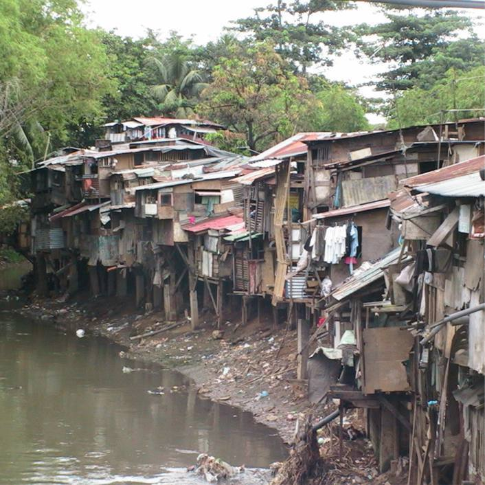 Disheveled homes of impoverished Filipino people on the banks of a creek.