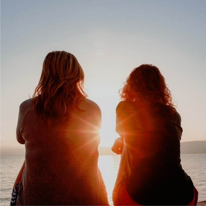 two women sitting on a beach talking with sun setting