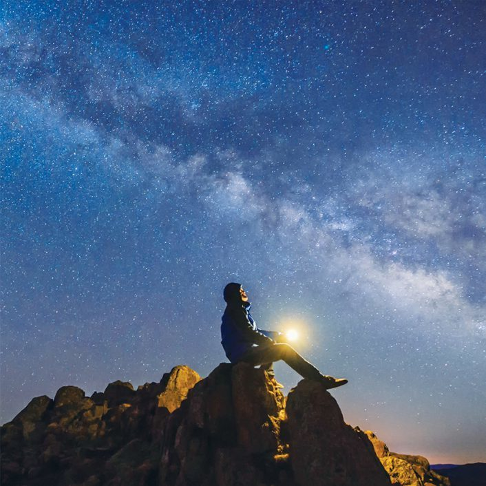 Man sitting on cliff looking into dark blue, starry sky.