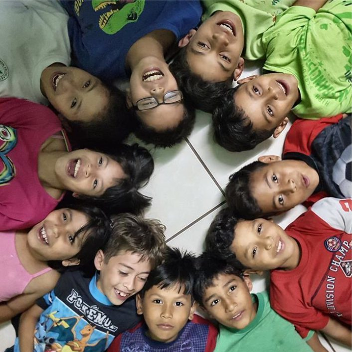 Smiling Honduran children laying on their backs in a circle with their feet meeting in the middle.