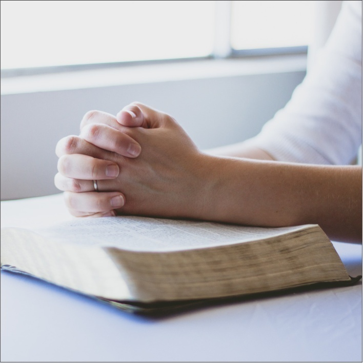 Female hands crossed in prayer over the open Bible.