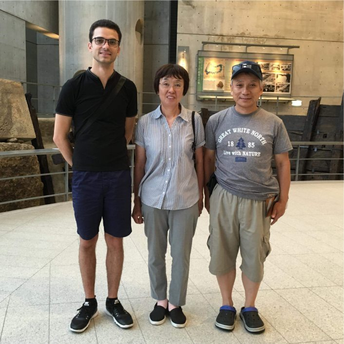 Man standing with an Asian couple in a museum.