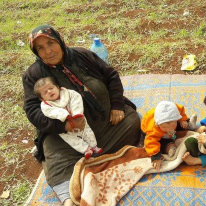 Syrian woman sitting on ground with baby and child