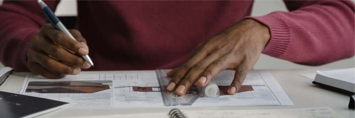 Table top image of a man sitting at a table working on building plans
