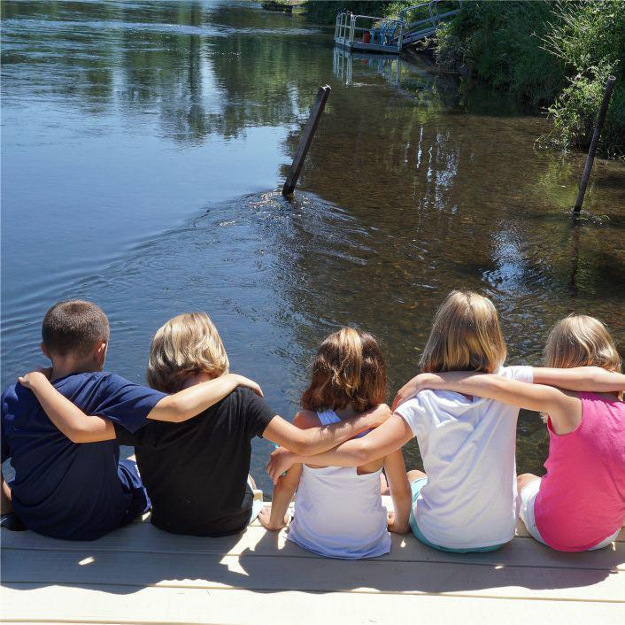 kids with arms around each other's shoulders sitting on a dock near water